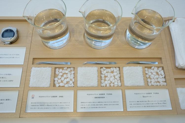 体験コーナーに並べられているタオル片。左から「今治タオルブランド 品質基準 合格品」「不合格品(柔軟剤使用過多)」「不合格品(糊抜き不十分)」。これらを水に浮かべると……?(撮影=下元陽)
