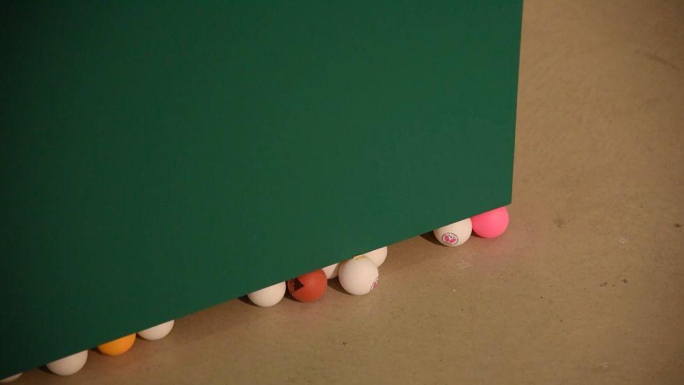 作品から目線を外し足元を見ると、床と什器の間に挟まっている卓球のボールに気が付く。細部にまでユーモアがちりばめられている