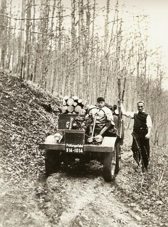 1946年10月に木材を搭載したプロトタイプを山間でテストドライブする設計者のハインリヒ・レーシュラーと、隣りに「ウニモグ」の名称を考えたハンス・ツァーベル