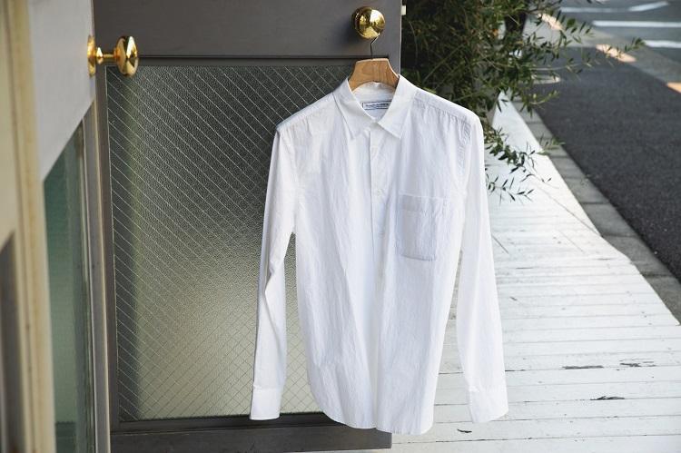 UNIVERSAL PRODUCTSのレギュラーカラーシャツ。ハリのあるタイプライター生地を使用した一枚。前立てのないデザインで上品さとカジュアルさを兼ね備える
