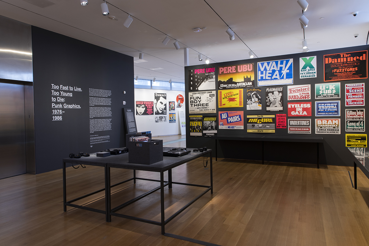 中央のテーブルにパンク・ロックのレコードとターンテーブルが置いてあり、視聴することができる。 Installation view of Too Fast to Live, Too Young to Die: Punk Graphics, 1976-1986 at the Museum of Arts and Design, New York (April 9–August 18, 2019). Photo by Jenna Bascom