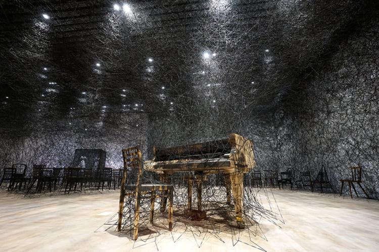 《静けさのなかで》 2002/2019年 焼けたピアノ、焼けた椅子、Alcantaraの黒糸 サイズ可変 制作協力:Alcantara S.p.A. Courtesy: Kenji Taki Gallery, Nagoya/Tokyo 展示風景:「塩田千春展:魂がふるえる」森美術館(東京)2019年 撮影:Sunhi Mang 画像提供:森美術館