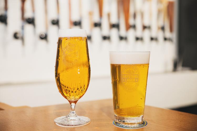 「BAYSTARS ALE」(左)と「BAYSTARS LAGER」(右)。横浜DeNAベイスターズの選手、監督、コーチに、「色」「アルコール度数」「ホップの香り」「苦味の程度」など細かくアンケートを取って作ったこだわりのビール。ともにパイント=800円、ハーフ=500円