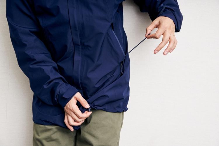 外側のポケットに手を入れた状態で裾のドローコードを制御可能。引くだけで締まり、留め具を押せばリリースされる