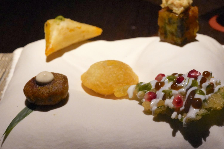 揚げた紫蘇にタマリンドチャッツネとザクロをあしらった「チャート(右下)、プルーン、マンゴーパウダー添えられた「鴨(かも)のケバブ」(左下)、バターチキンを入れたサモサ(左上)、エビとワサビが添えられた、ひよこ豆のケーキ「ドクラ」(右上)