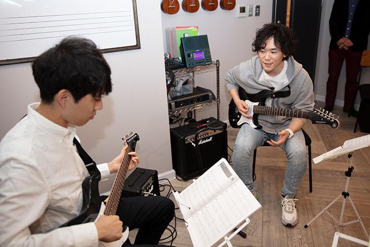 「その人に合ったコードの押さえ方をアドバイスしています」と平島慎吾先生(右)