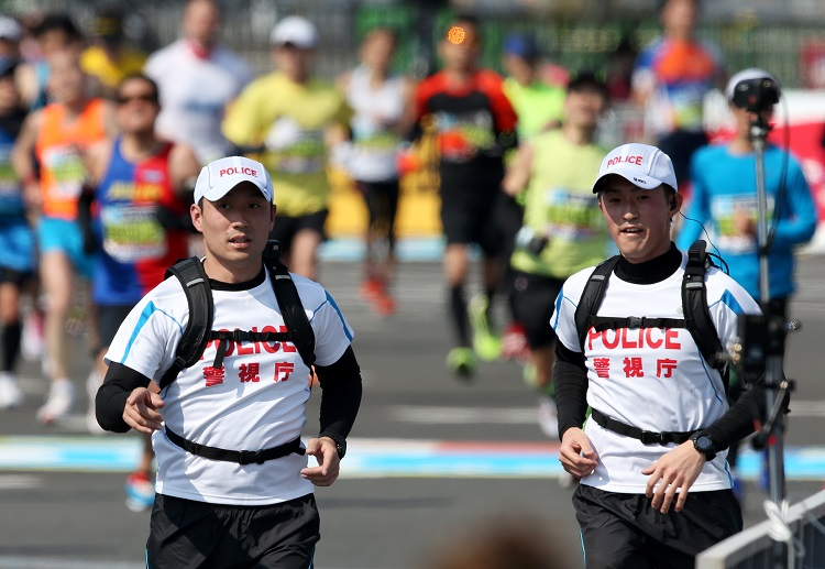 ランナーと同じコースを走りながら警備する「ランニングポリス」=2016年2月28日午後、東京都江東区有明3丁目、林敏行撮影