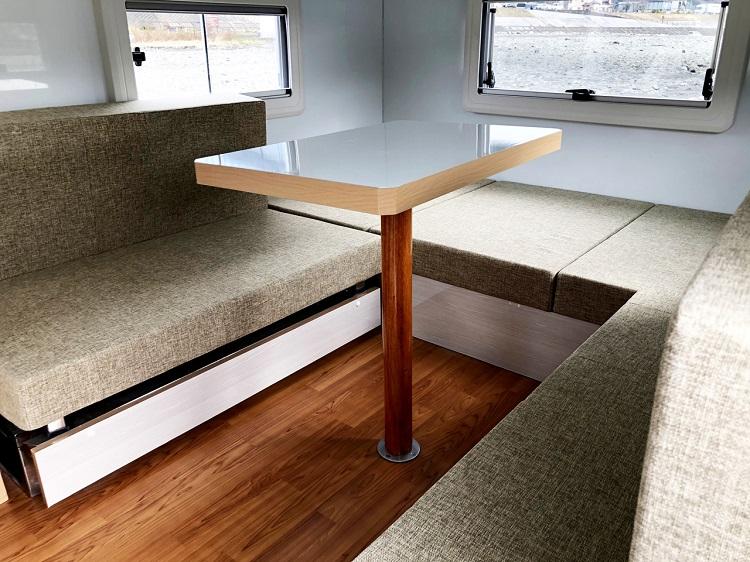 リビングスペースはコの字のシンプルな構成。標準仕様では右サイドのソファーが横向き2名の乗車スペースに