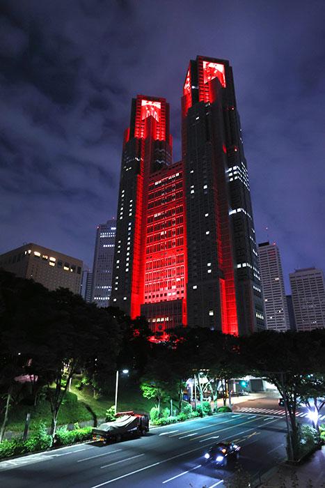 「東京アラート」の発動を受けて警戒を呼びかける赤色にライトアップされた東京都庁=6月2日、長島一浩撮影