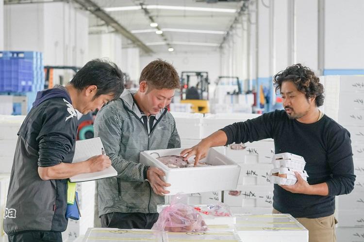 仲買と農家が、鶏の餌にする魚と野菜を物々交換している様子を取材する高橋(左)=福島県相馬市
