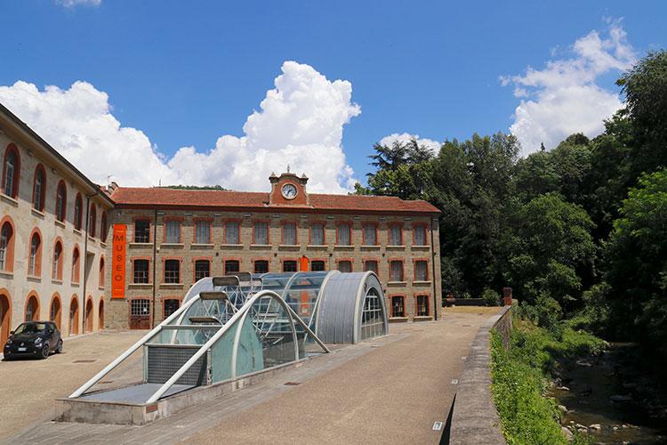 旧・羊毛加工場の建屋を改装して開館した毛織物工芸博物館。手前のガラスの中にあるのは、脇に流れる川を使った水力発電のタービン。かつて織機の動力に用いられていた