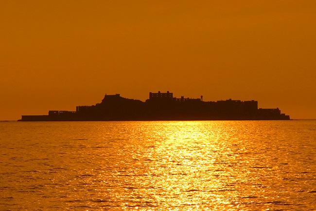 夕日に軍艦のようなシルエットを浮かび上がらせる端島