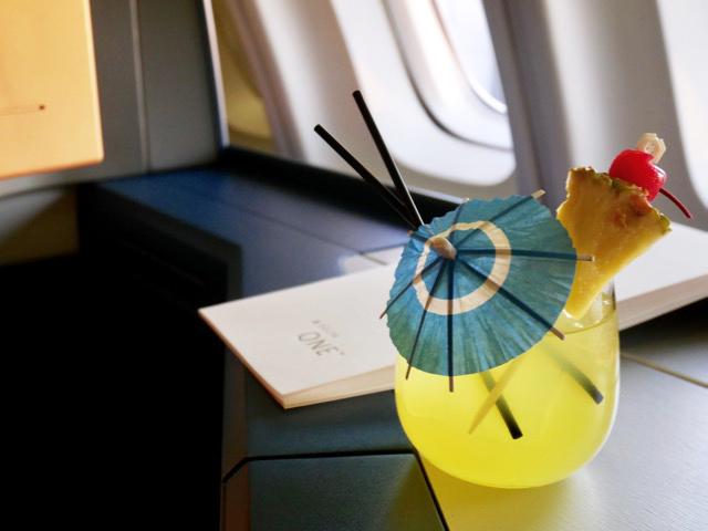 デルタ航空の日本発ハワイ行きの機内でだけ味わえるカクテル、マイタイ。出発前からリゾート気分に満ちています。2階建てジャンボ機の2階席には、人生初のビジネスクラスに乗る新婚さんがアメリカ人クルーに大歓迎されていました