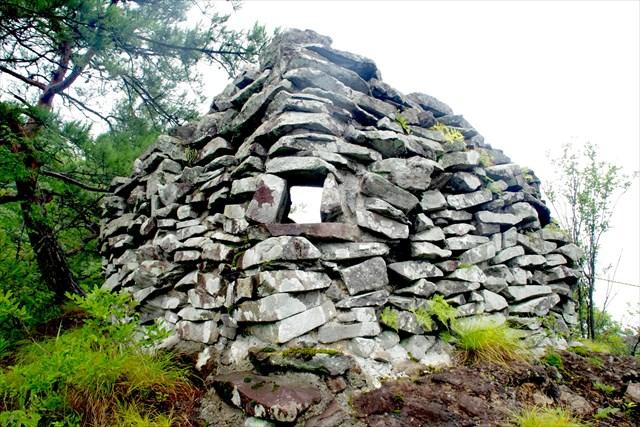 全国でも類を見ない、石積櫓(楕円形石積遺構)。3か所の穴は銃眼ともいわれるが、後世のものとも考えられ、真意は謎。石積櫓からはしごで降りた先にはさらに石塁があり、二重の防備となっている