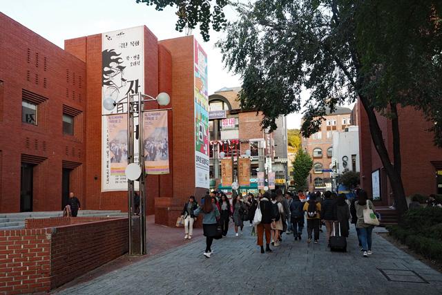 大学路の街角。劇場公演の垂れ幕や看板の前を多くの人が行き交う