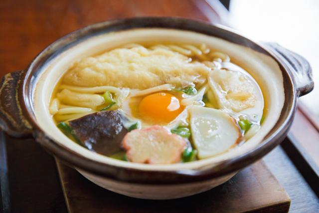 名物「冨美家鍋」(720円・税込み)はえび天、焼き餅、カマボコ、しいたけ、卵の入った鍋焼きうどん。