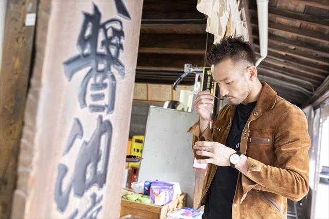 看板商品「ヤマブン本醸造特選醬油」を味見する中田さん