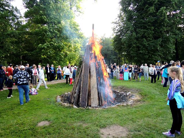 焚き木の周りに人々が輪になって集まり、歌いながら点火の儀式が行われる