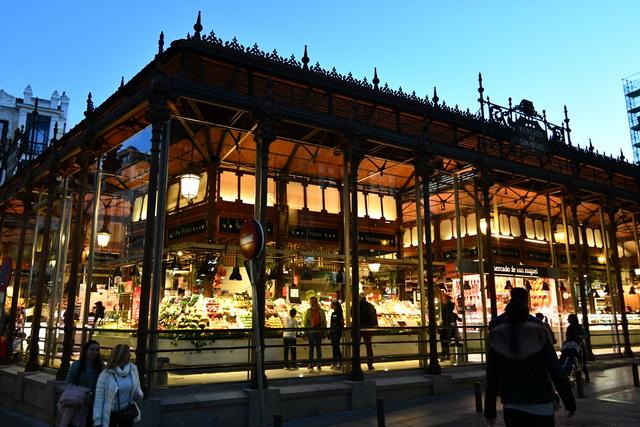 夜のサン・ミゲル市場。建物内の照明が浮かび上がり、ライトアップされたように見える