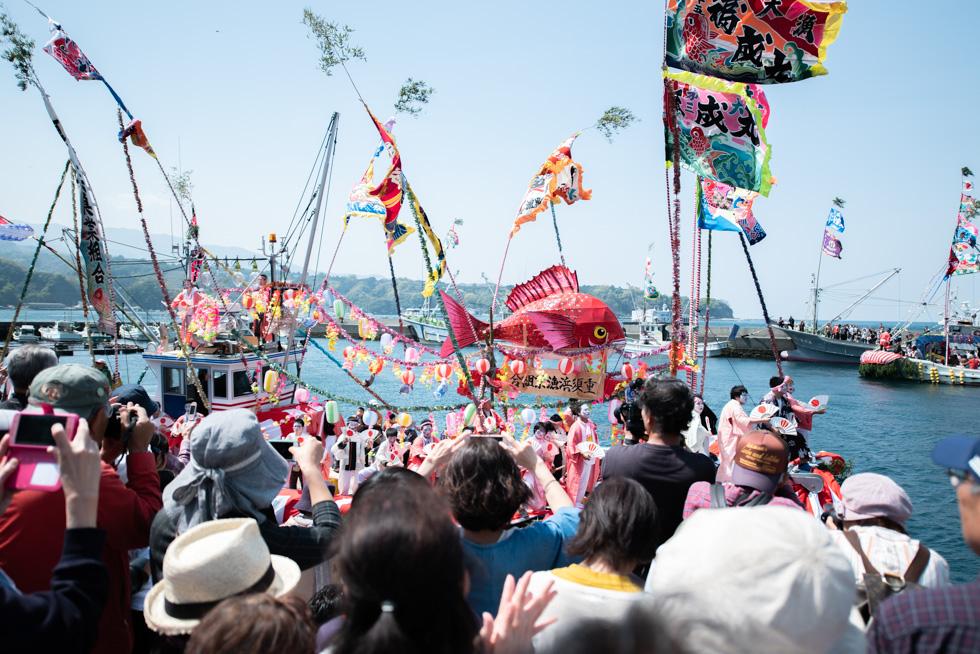 大瀬崎から内浦漁港に戻った踊り船は、ミカンや餅などを振る舞うことも