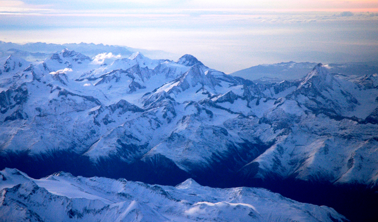 飛行機の窓から雪と氷に覆われたアルプスの山々の美しさに見とれます