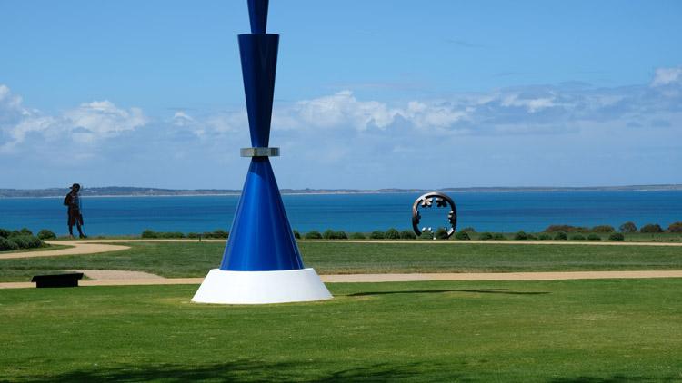 様々な彫刻作品が設置された庭園。その先には真っ青に輝くウェスタン・ポート湾