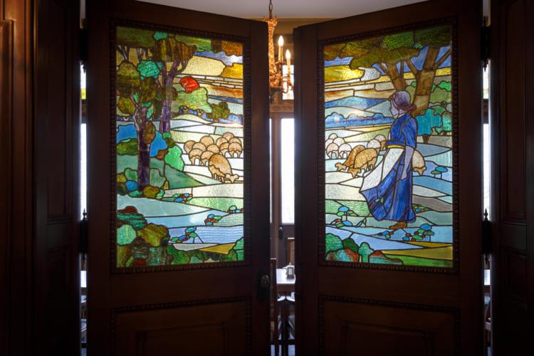 羊飼いが描かれたステンドグラスの扉。室内の窓のステンドグラスと絵柄がリンクしている