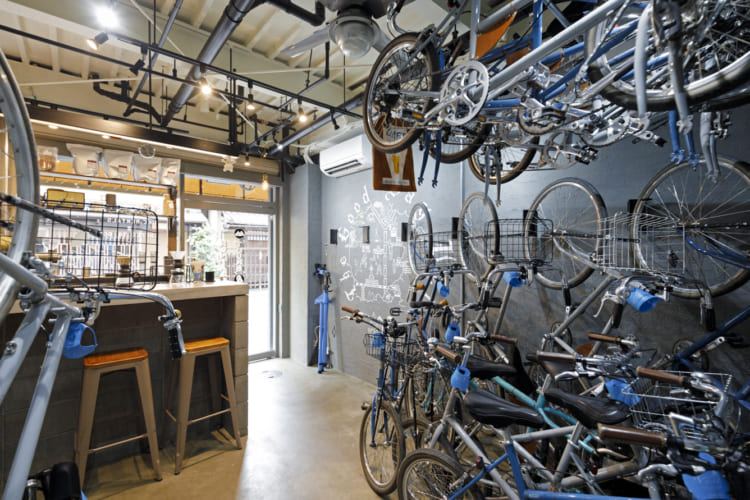グレーやブルーを基調とした内装に、天井や壁にも自転車が収納された武骨な空間は、アメリカ西海岸のサイクル&カフェショップのよう