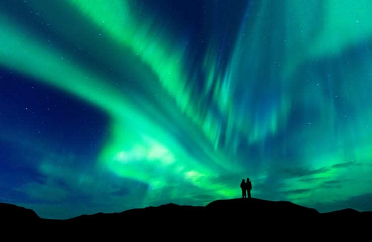 Aurora borealis with silhouette love romantic couple on the mountain.Honeymoon travel concept