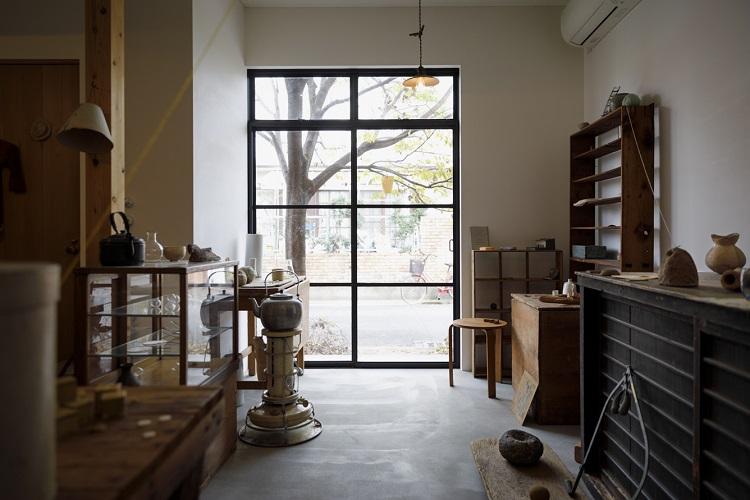 鉄格子の扉から光が注ぐ空間。日本のものを中心に、縄文土器から戦後の雑器まで自由な目線で選ばれたものが並ぶ