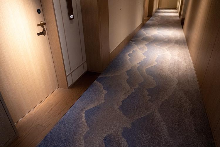 廊下のカーペットは、奈良の山々の稜線をイメージしたもの。ライトの当たり方まで計算されているかのよう