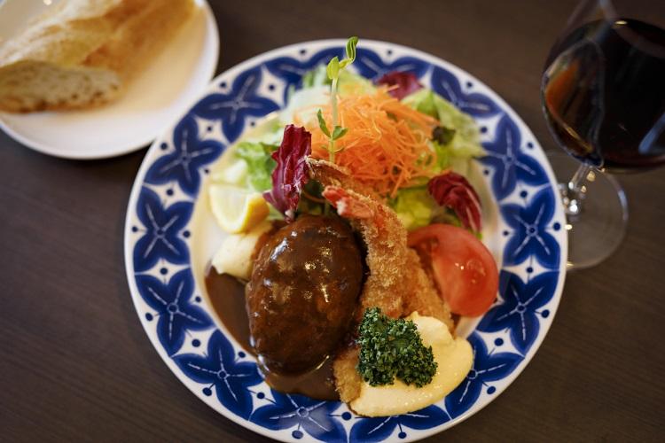 「ハンバーグ(130g)とエビフライ(2尾)」(1500円、税込み)。サラダとパンのほか、ランチはドリンクが付く。ワインも選べるのがうれしい