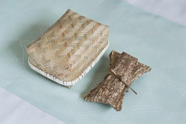 かご風のお弁当箱におかず、竹皮におむすびを入れて、品のよいピクニック風に