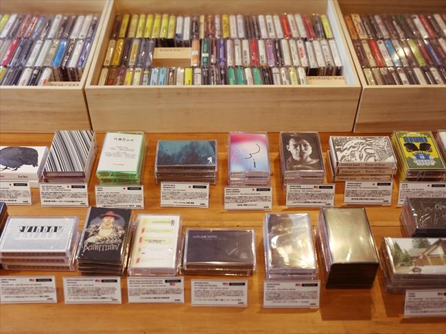 カセットテープのディスプレイは、オシャレな本屋で見掛ける平積みを意識したという。「中古レコード店とか古本屋って、棚に雑然と並べられたイメージがあるけど、それよりもアートギャラリーのようにしたいと考えました。女性がひとりで気軽に入れる店にしたかったんです」(角田さん)