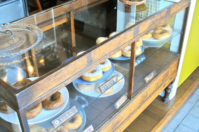 ドーナツの入った木製のケースに向かい合ってパンを買う