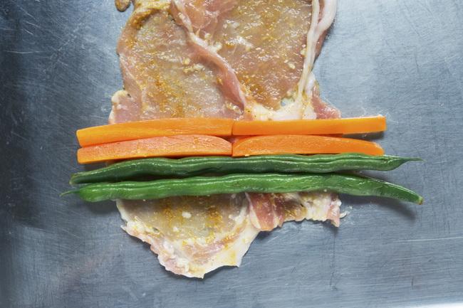 野菜の肉巻きは、豚ロース薄切り肉2枚を少しずらして重ね、そこに野菜をのせてしっかり巻きます。巻き終わりを水溶き小麦粉でのり止めすると、きれいに焼きあがります