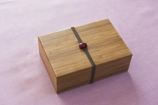 お弁当箱は四角くキュッと小さいながらも、綺麗な佇まいのものを選びました。蓋が開かないようにするためのゴムの飾りも可愛らしいです