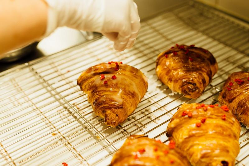 パティスリーで販売するクロワッサンを焼くのも狭間さんたちの仕事。<ピエール・エルメ>の代表作でもある「イスパハン」(マカロンにライチとフランボワーズ、バラ風味のフリームをサンドしたケーキ)にちなんだクロワッサンにはフランボワーズのコンポートとライチが入っている