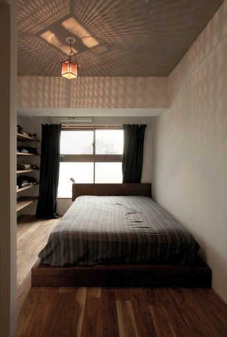 美しい影を作る照明が印象的なベッドルーム