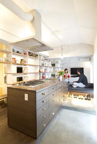 玄関から続くモルタルの土間。木製のキッチンは家具のような存在感