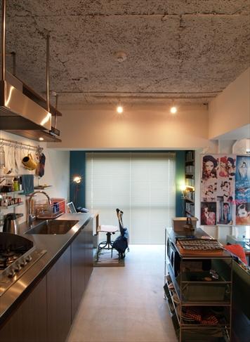 キッチンは壁付けにして部屋全体を広く見せた。奥の青い壁が印象的