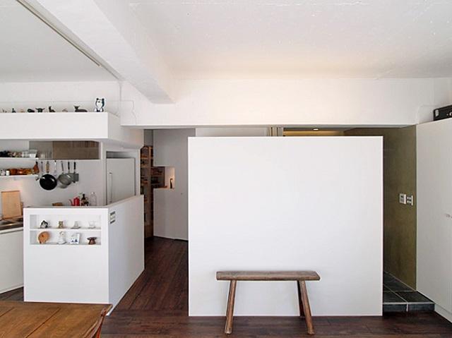 白い壁の向こう側に洗面台とバスルームがある