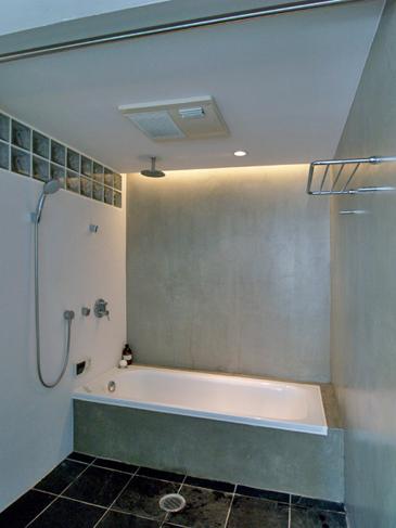 間接照明でリラックスできるバスルーム。壁はモルタル仕上げ