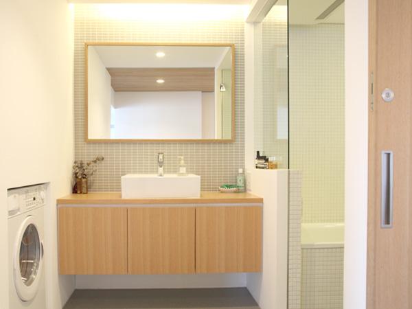 清潔で暖かみのある洗面所。ガラスの向こうが浴室