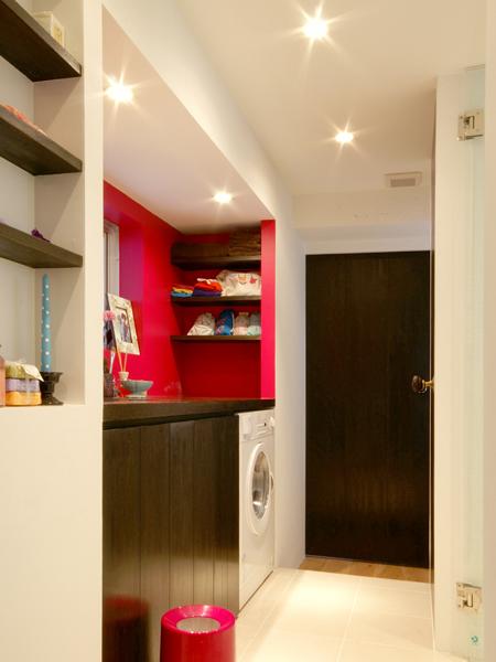 洗面スペースなどは赤でペイント。奥が納戸、右側がバスルーム、手前が玄関ホールだ