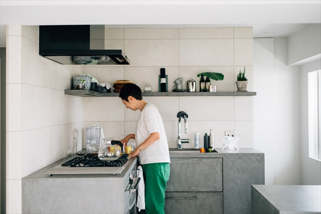 自宅のキッチン。冷蔵庫や電子レンジなど生活感が出るものはリビングから見えない左奥のスペースに収納できるように設計した。「大きな家電や食器棚をできるだけ見えないようにすると、家がぐっと広く感じるんです」