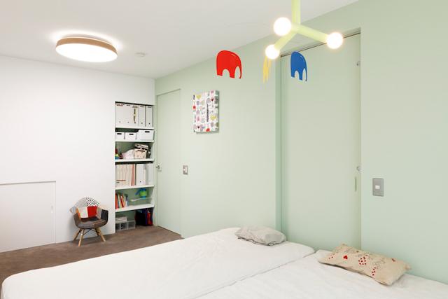 淡いグリーンの壁がやさしい雰囲気の寝室。将来2部屋に分けられるよう扉は二つ