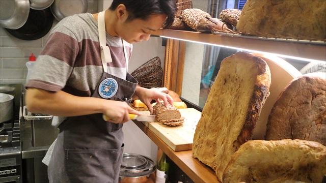窓際に積まれたパンを薄くスライスしパン盛りが作られる