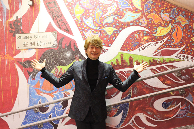 香港で描いた壁画のレプリカの前に立つ香取慎吾さん