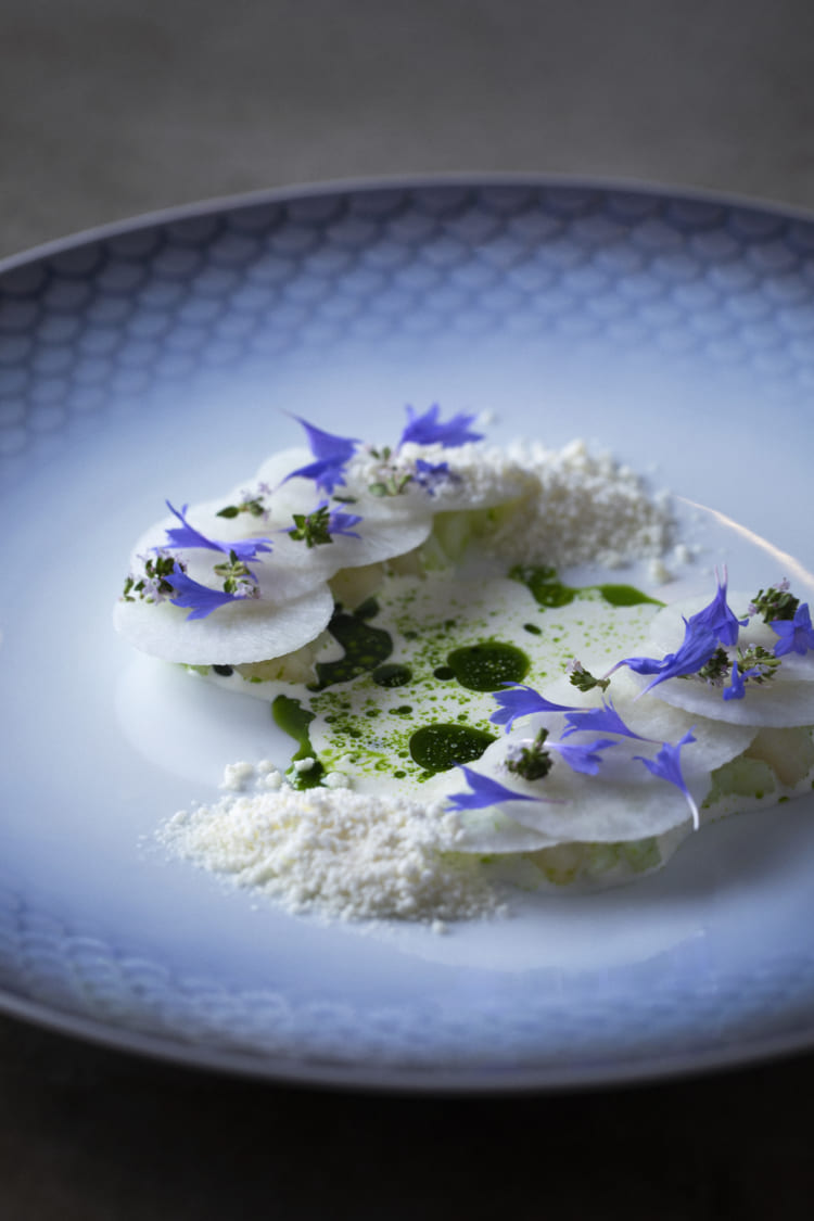 真っ白な大根と青い花のハーブが爽やか。大根の下には宮城県唐桑漁港で獲(と)れるうま味とミネラル感たっぷりの新鮮なホタテが